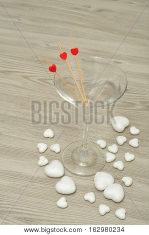 Valentines day-A martini glass with three sticks decorated with red hearts and polystyrene hearts