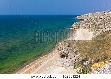 hilly sea coast with rocks and blue sky
