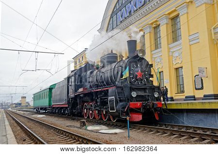 Kharkiv Ukraine - November 4 2016: Restored steam locomotive Er-794-12 and retro passenger car near the platform of railway station
