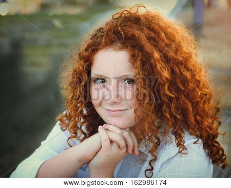 Pretty redhead young girl with curly hair portrait outdoors