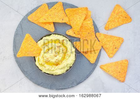 Healthy avocado hummus sprinkled with olive oil paprika and sesame served with nachos horizontal top view