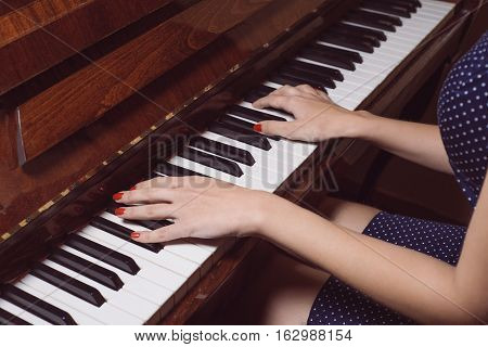 Beautiful female hands on the keys of an old piano. close-up