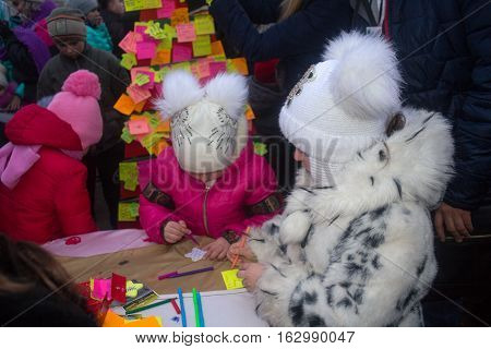 Donetsk Ukraine - December 23 2016: Children write on labels on a symbolic tree on Lenin Square with the wishes of the world