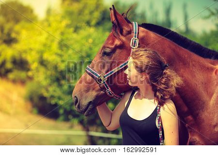 Taking care of animals love and friendship concept. Jockey young girl petting and hugging brown horse on sunny day