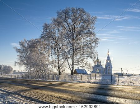 Orthodox white church with golden cupola and bell-tower next to the country road in sunny winter day