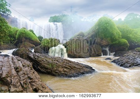 Amazing view of waterfall with yellow water among green woods on dramatic sky background in Dalat Vietnam.