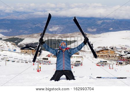 young happy man in winter clothes and ski gear posing happy in snow mountains at Sierra Nevada resort in Spain in adventure sport and vacation destination concept
