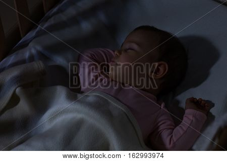 Baby Sleeping on the bed. Adorable baby sleeping at night. Little girl in pajama taking a nap in dark room.