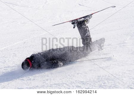 young unskilled man falling on cold snow in ski crash at Sierrna Nevada resort in Spain in winter sport accident concept