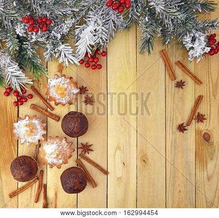Fragrant cupcakes with spices and cinnamon sticks star anise and tree branch in the snow red berries. The festive mood. Home kitchen. Comfort. Tradition and family values.Top view.