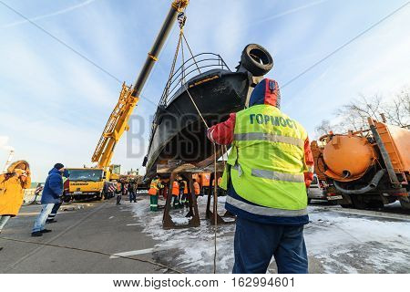 MOSCOW, RUSSIA - NOVEMBER 11, 2016: State Unitary Enterprise Mosvodostok performs recovery vessels on coastal winter parking. Workers install boat on the metal supports.