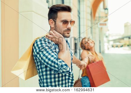 Man bored shopping with his girlfriend in the city.