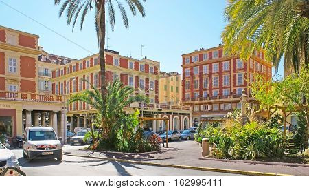 MENTON FRANCE - FEBRUARY 22 2012: The lush green garden with palms among the ochre buildings in Ardoino Square on February 22 in Menton.