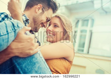 Portrait of young beautiful stylish couple in the city.Young happy couple hugging and laughing.