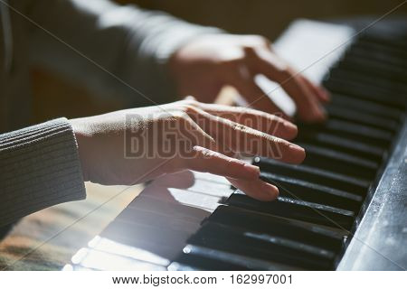 The small children's hands playing the piano close up