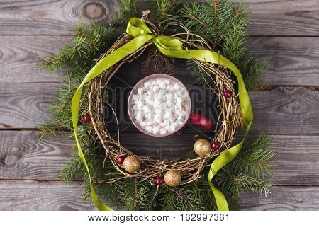 Flat lay cup of cocoa with marshmallows in the middle of a Christmas wreath