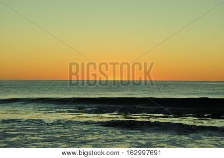 clear sky sunrise glassy surf in forefront