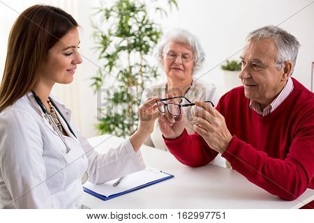Doctor Ophthalmologist Giving Glasses To Patient After Eyes Exam