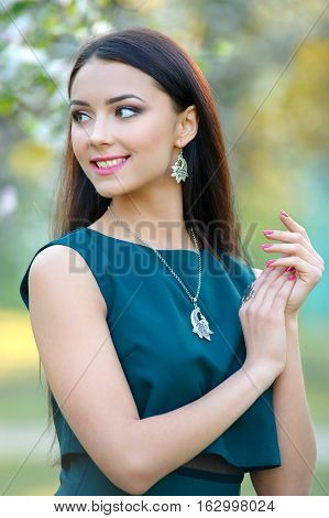 long hair girl model with luxury accessory and jewelry. Perfect view background blooming garden