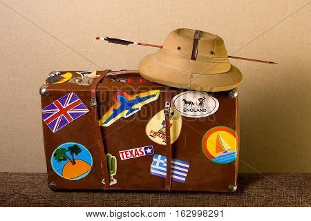 Old battered suitcase seasoned traveler with stickers from various countries he visited tropical helmet and broken through arrow.