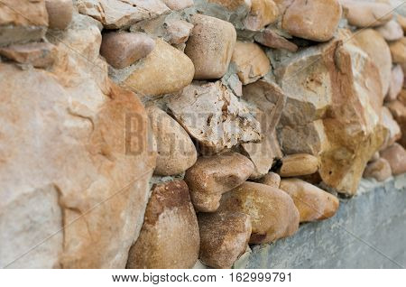 shapeless stones wall with smooth edges. Texture background.