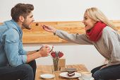 Eat this. Happy loving couple is dating in cafeteria. Woman is feeding her boyfriend with sweet cake. Man is holding cup of coffee and laughing poster