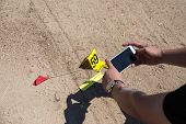 law enforcement or forensic take picture of evidence from car bomb with marker and ruler by smart phone in post blast investigation training poster