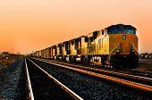 Cargo locomotive railroad engine crossing Arizona desert wilderness during sunset