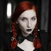 Portrait of red-haired girl in bow tie on a dark background gothic style girl with pigtails a girl in a black dress fashion style sense of style girl in dress and in a black cloak black coat black lips sitting poster