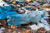 Pile of plastic bags and other refined petroleum products dumped in landfill. Garbage heap gives infiltrate into groundwater. Waste sorting is required. Blue plastic bottle, poster