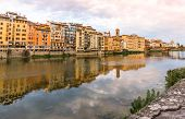 Houses and bridge on the Arno river with reflections poster