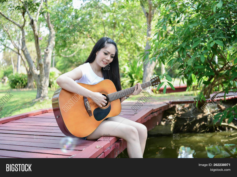 Asian Girls Playing Guitar. Asian Women Relaxing With Music. Asian Women