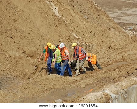 Group of construction workers dragging machinery at construction work