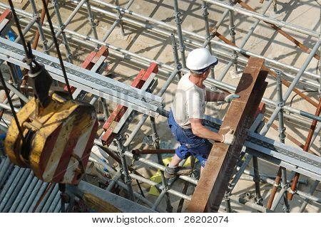 Construction worker unloading steel beam on scaffolding