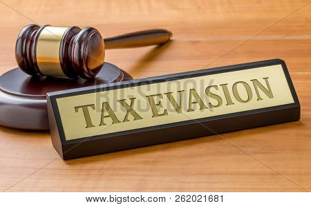 A Gavel And A Name Plate With The Engraving Tax Evasion