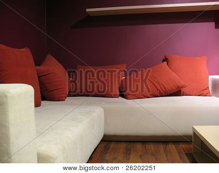 Purple wall living room with modern light beige sofa and five red pillows
