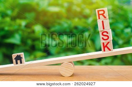 Wooden House And Cubes With The Word Risk On The Scales. The Concept Of Risk, Loss Of Real Estate. P