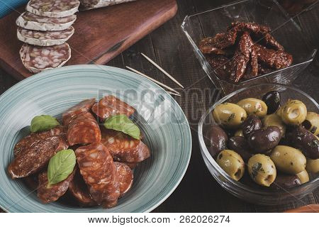 Chorizo And Salami Sausages On Bowls And Cutting Board With Dried Tomatoes And Olives. Bar Ready For