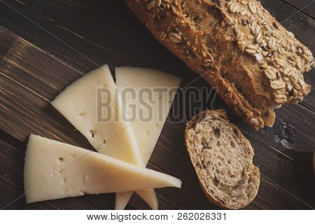 Top View Of Wooden Table With Spanish Manchego Sheeps Cheese And Multigrain Bread. Vintage Effect