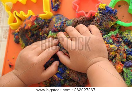 Hands Of Child Playing Multicolored Kinetic Sand. Children Activity Game Toy For Model Forming Craft