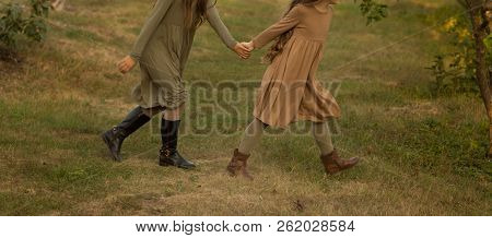 Two Girls, Teenagers, Holding Hands, Walk On Green Grass, Side View.in A Brown And Green Dress, Autu