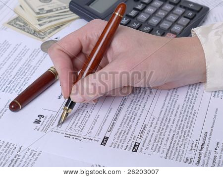 Female hand filling out W-9 income tax form with pen