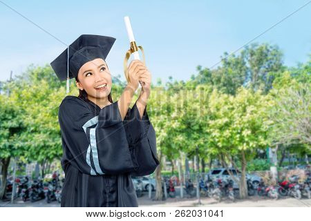 Beautiful Asian Student Girl Celebrate Her Graduation With Cap And Diploma Scroll On Campus