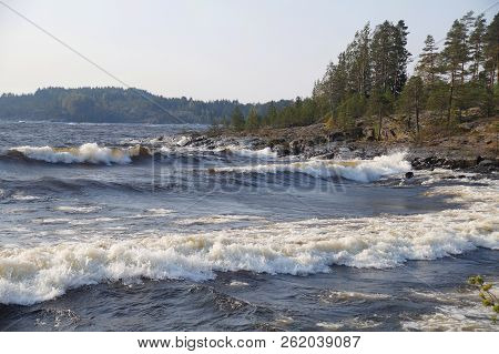 The Bay Of The Lake With Foaming Waves On A Clear Windy Day. The Rocky Shore Is Covered With Forest.