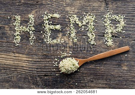 Word Hemp Made Of Hemp Seeds On Old Wooden Background. Organic Blanched Hemp Seeds In A Spoon On Rus