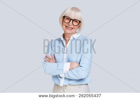 Great Expertise. Beautiful Senior Woman Looking At Camera And Smiling While Standing Against Grey Ba