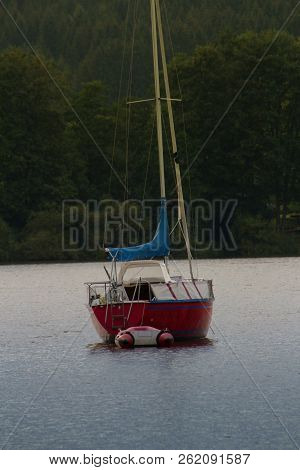 Small Boat - Sailing Boat In The Harbor. A Small Boat With Sail Docked In The Harbor.