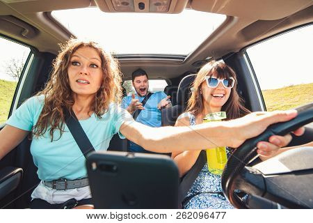 Group Of People In Car. Woman Driver Drinking Water And Don't Look On The Road.
