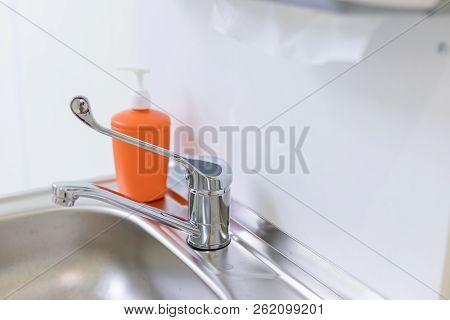Orange Bottle For Liquid Soap In Dentist, Doctor Office. Metal Sink, Liquid Soap, Paper Towels.healt