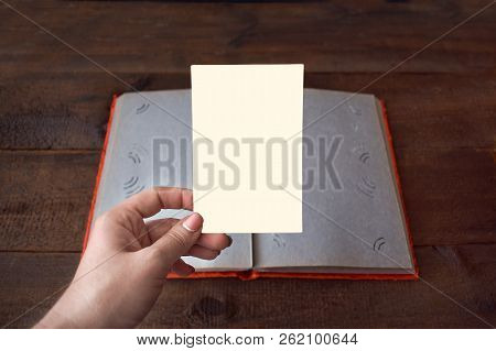 Women Hand With Empty Pictures On Photo Album On Wooden Table Background. Vintage Book Or Photo Albu